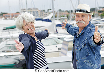 elderly couple showing open arms in the sea