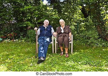 elderly couple sitting hand in hand in their garden