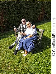 elderly couple sitting in their garden and enjoy life