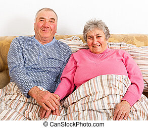 Elderly couple sitting on bed