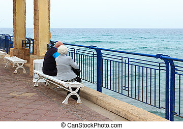 Elderly couple sitting on the sea in the early morning