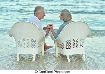 Elderly couple sitting on the shore and looking at each...