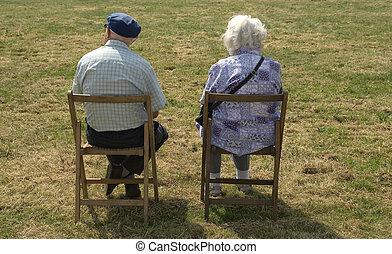 Elderly couple sitting quietly in field