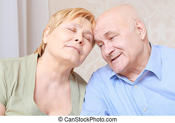 Elderly couple sitting together - Happy together. Elderly...