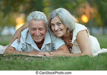 Elderly couple smilling together over natural background