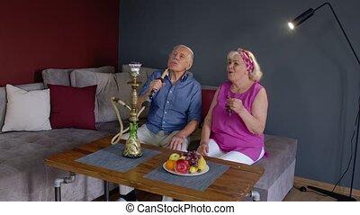 Elderly couple smoking hookah at home. Senior grandmother and grandfather having fun, relaxing