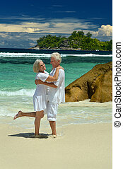 Elderly couple standing on the beach embracing