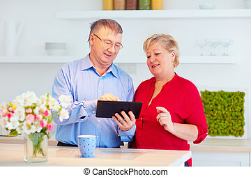 elderly couple surfing online on tablet, at home