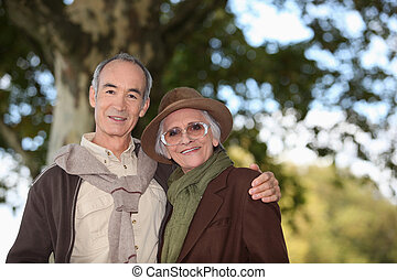 Elderly couple taking a walk together in the forest