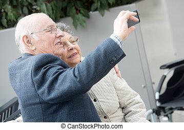 elderly couple taking selfie