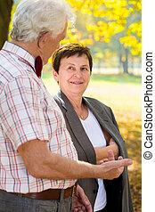 Elderly couple talking in park