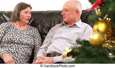 Elderly happy couple talking near a Christmas tree. They are out focus and then comes in focus when camera close to them.