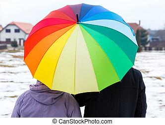Elderly couple under colorful umbrella