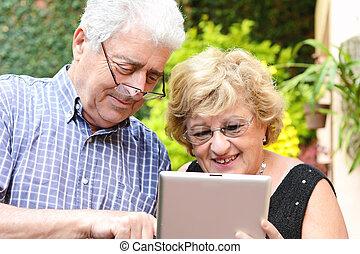 Elderly couple using tablet.