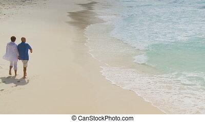 elderly couple walking along beach 002 part I