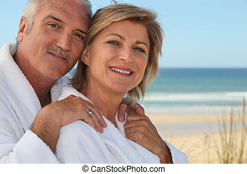 Elderly couple wearing white at the beach
