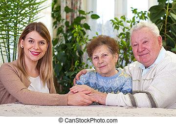 Elderly couple with happy caregiver