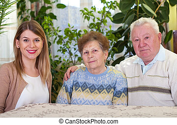 Elderly couple with happy caretaker
