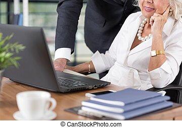Elderly couple working on laptop