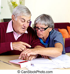 Elderly couple working with documents and taxes
