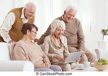 Elderly couples looking at laptop