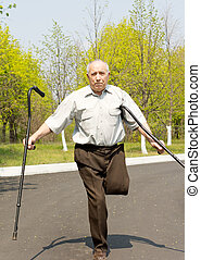Elderly disabled man balancing on one leg