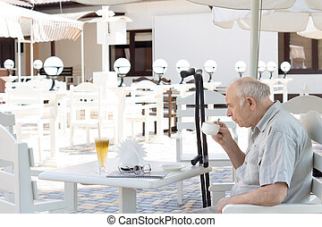 Elderly disabled man enjoying a cup of coffee