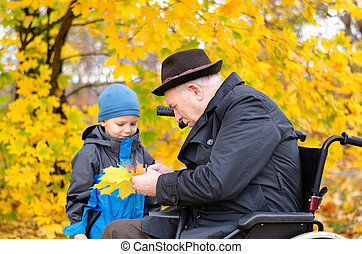 Elderly disabled man playing with his grandson outdoors