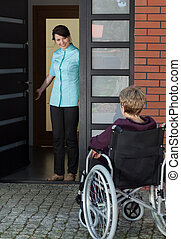 Elderly disabled woman enters the house