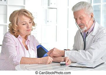 Elderly doctor measuring blood pressure of woman