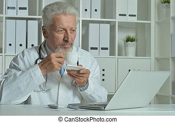 Elderly doctor with  laptop