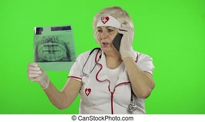 Portrait of elderly caucasian female doctor talking on the phone with client. Female nurse with radiogram, x-ray. Dentist. Green screen. Chroma key