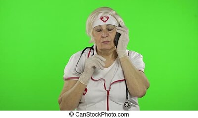Elderly female doctor talking on the phone with patient. Coronavirus. Covid-19