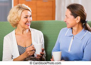 Smiling elderly female having coffee break at office. Focus on blonde woman