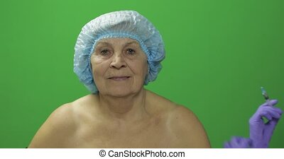 Elderly female in protective hat. Doctor making facial injections for patient