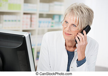 Elderly female pharmacist chatting on the phone