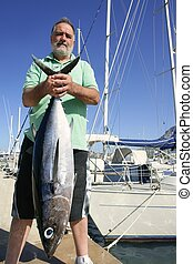 Elderly fisherman with Albacore tuna catch in hands