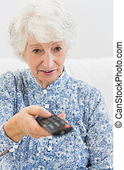 Elderly focused woman using the remote