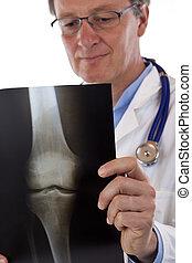 Elderly friendly doctor studies knee x-ray carefully.