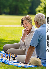 Elderly friends couple playing chess outdoors