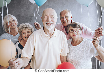 Elderly friends enjoying birthday party - Smiling elderly...