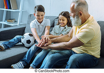 Elderly gentleman and grandchildren getting motivated before playing football