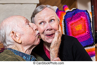 Elderly Gentleman Kissing Elderly Woman on Cheek