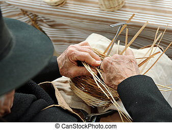 elderly gentleman makes a wicker basket