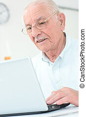 Elderly gentleman using a laptop