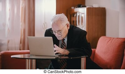 Elderly grandfather - old grandfather is typing something hunched over a computer