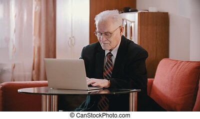 Elderly grandfather - old grandfather with glasses is typing on a computer