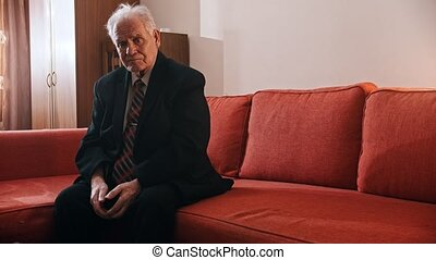 Elderly grandfather - sad old grandfather is sitting on a sofa
