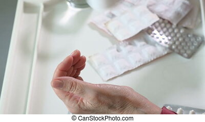 Elderly grandmother takes pills at home