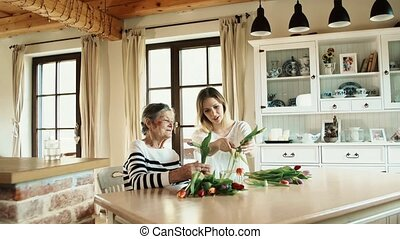 Elderly grandmother with an adult granddaughter at home., putting flowers in a vase.